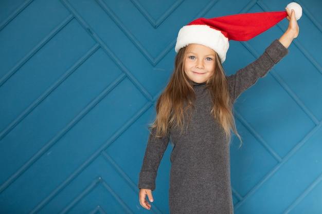 サンタクロースの帽子をかぶっている愛らしいブロンドの女の子 無料写真