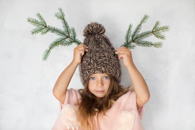 Смешная маленькая девочка позирует в зимней шапке Бесплатные Фотографии