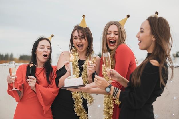 屋上パーティーで誕生日ケーキを保持している豪華な女の子 無料写真