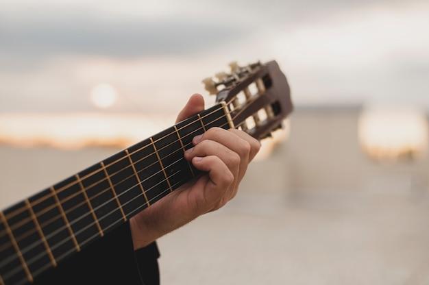 夕日の背景に屋上でギターを弾く男 無料写真