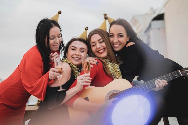 屋上パーティーでギターを弾く女性の幸せなグループ 無料写真