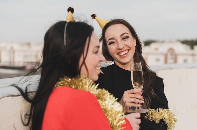 屋上のパーティーで笑顔の赤と黒のドレスを着た女性 無料写真
