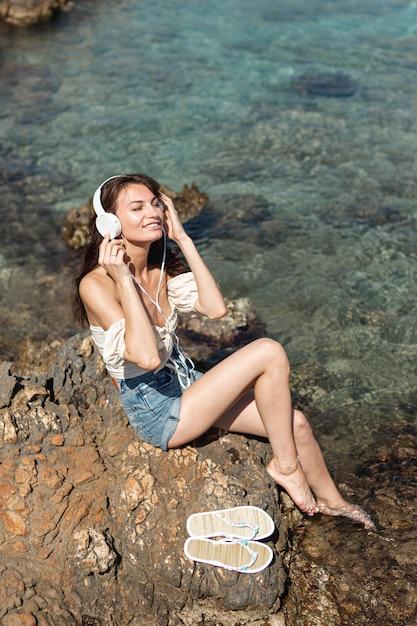 岩の上の音楽を聴く女性 無料写真