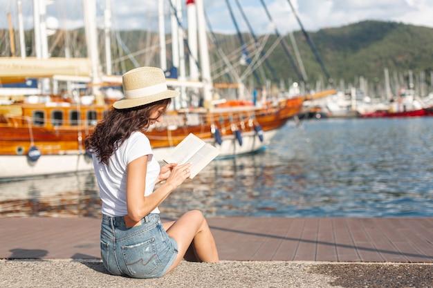 ポートで本を読んで若い女性 無料写真