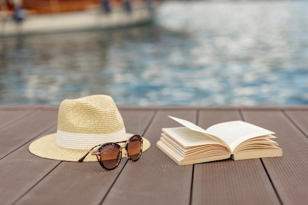 サングラスの本と港の岸に立っている帽子 無料写真