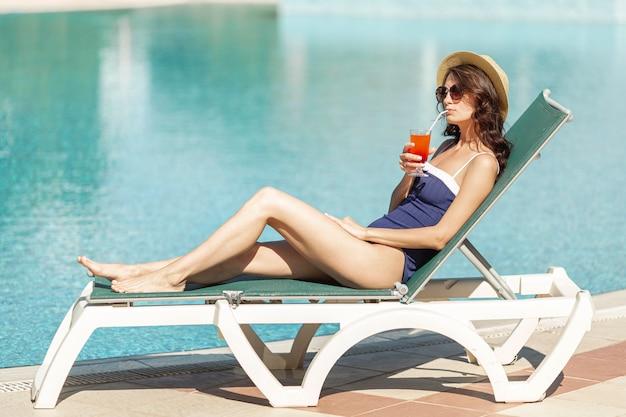 Женщина лежит на гостиной, наслаждаясь напитком Бесплатные Фотографии