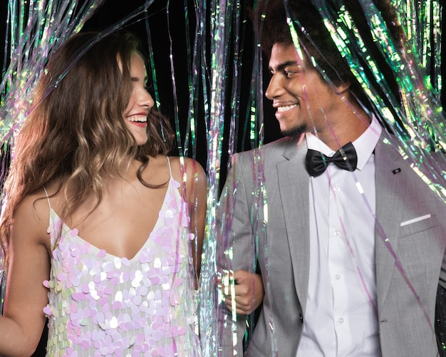 Милая пара, глядя друг на друга из шторки из блесток Бесплатные Фотографии