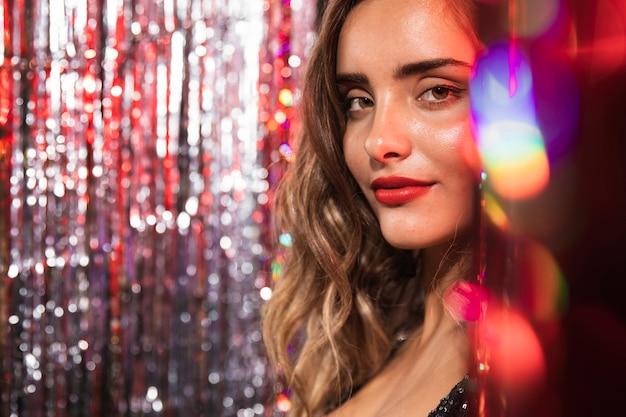 輝きのぼやけたカーテンに囲まれた少女 無料写真