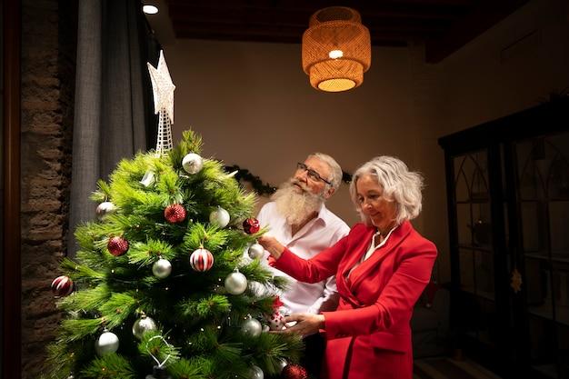 老夫婦のクリスマスツリーのセットアップ 無料写真
