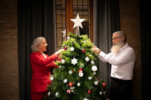 年配の男性と女性のクリスマスツリーのセットアップ 無料写真