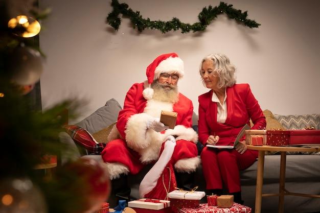 Санта-клаус и женщина готовы к рождеству Бесплатные Фотографии