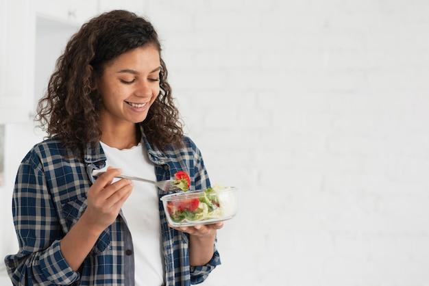 サラダを食べて笑顔のアフロアメリカンの女性 無料写真