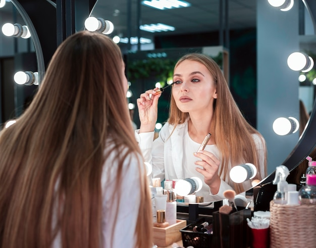 鏡を見てマスカラーを適用する女性 無料写真