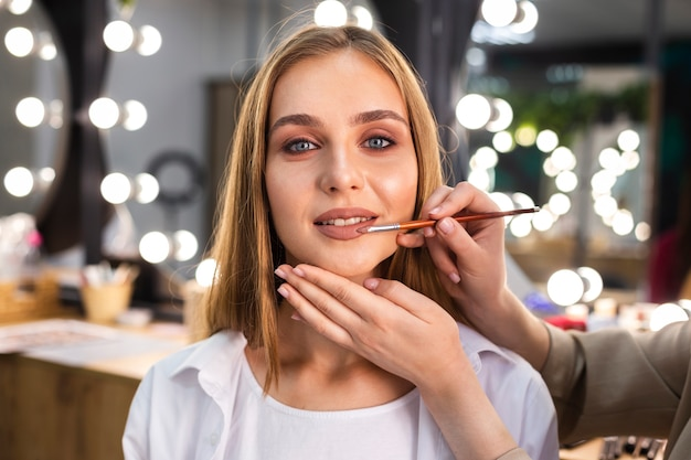 ブラシで笑顔の女性に口紅を適用するメイクアップアーティスト 無料写真