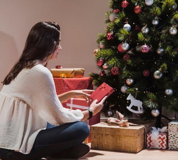 クリスマスツリーとギフトの隣に座っているサイドビュー女性 無料写真