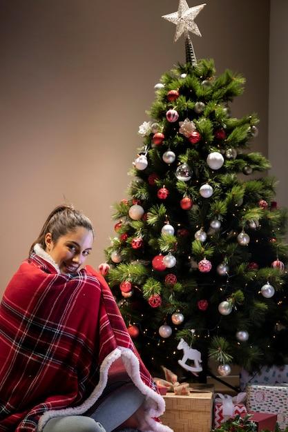 クリスマスツリーの横に座っている毛布を持つ若い女性 無料写真
