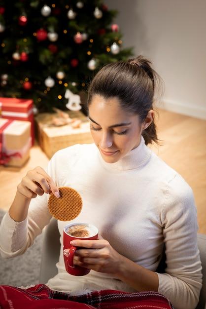 Брюнетка смотрит на чашку кофе Бесплатные Фотографии