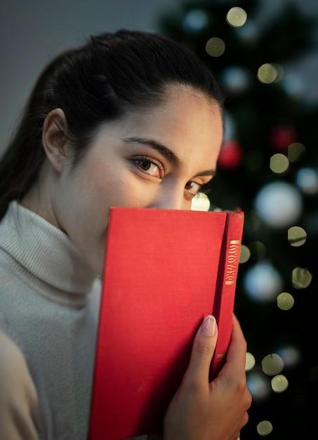 本で顔を覆っている美しい若い女性 無料写真