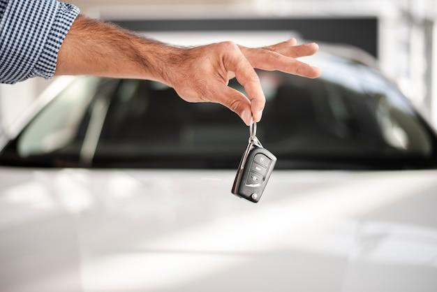 Рука крупным планом держит ключи от машины Бесплатные Фотографии