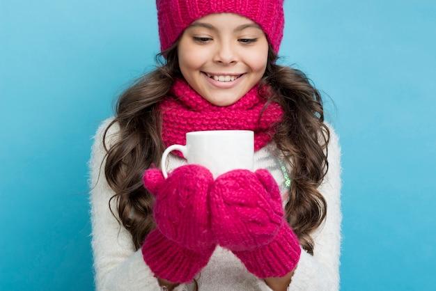 冬の服を着た少女の手でカップ 無料写真