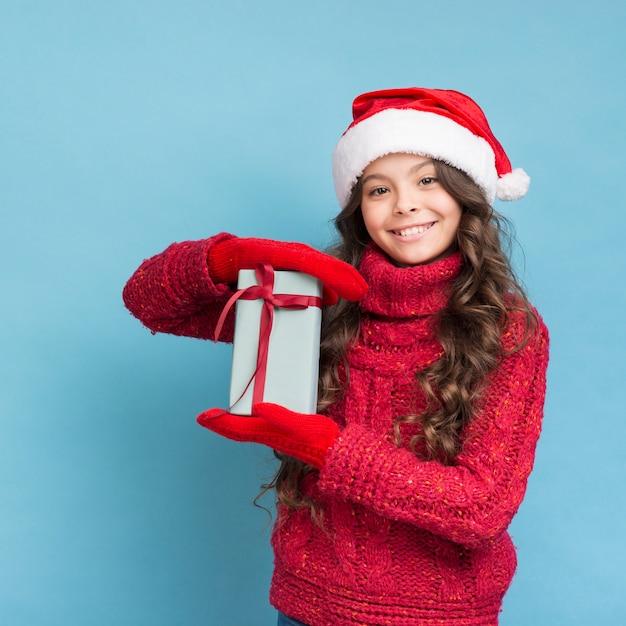 彼女の手に贈り物と冬服の女の子 無料写真