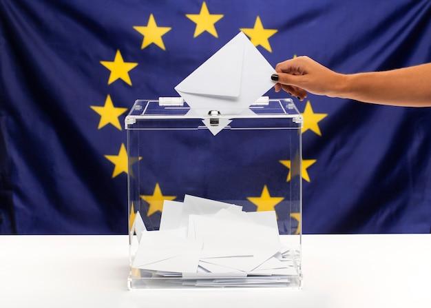 白い封筒と欧州連合の旗の正面でいっぱいの透明な投票箱 無料写真