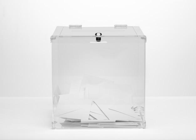 投票速報で満たされた正面の透明な投票箱 無料写真