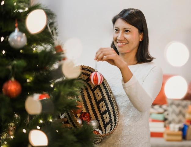 クリスマスツリーを飾る陽気な女性 無料写真