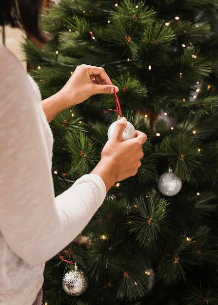 白いボールでクリスマスツリーを飾る女性 無料写真