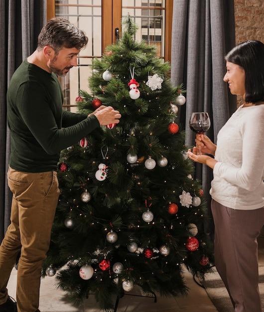 クリスマスツリーを飾る年配のカップル 無料写真