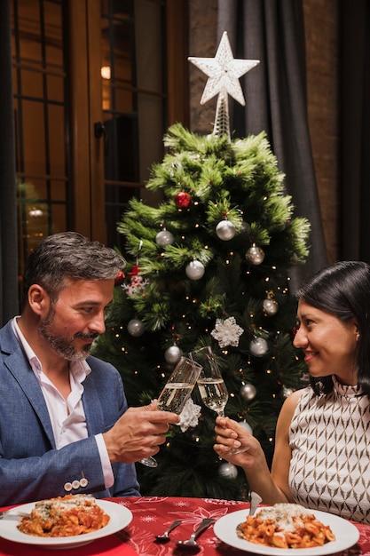 クリスマスディナーを祝う年配のカップル 無料写真