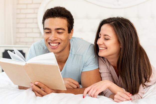 Средний выстрел смайлик пара читает в постели Бесплатные Фотографии