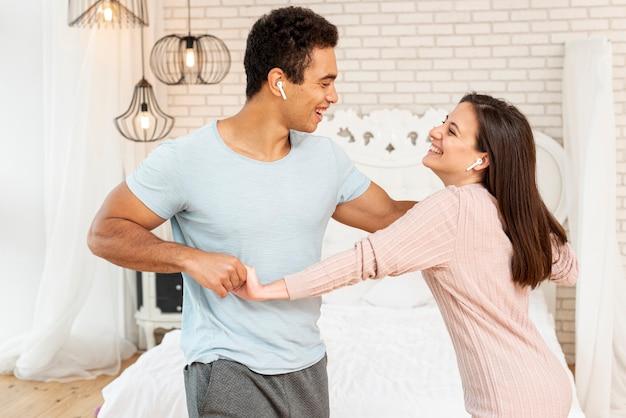 Средний выстрел смайлик пара слушает музыку в спальне Бесплатные Фотографии