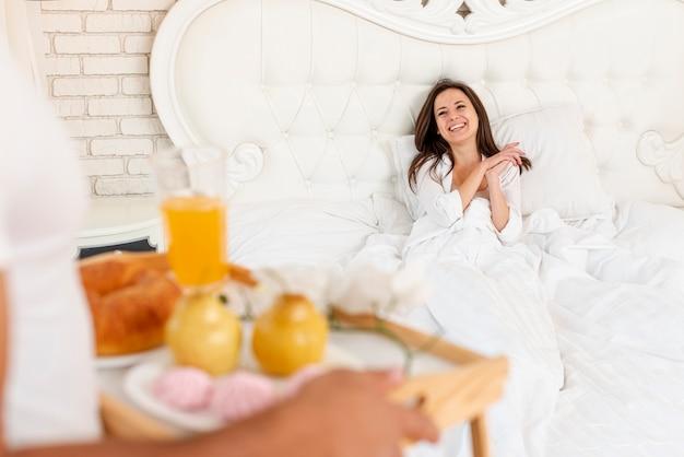 Крупным планом парень приносит завтрак своей девушке Бесплатные Фотографии