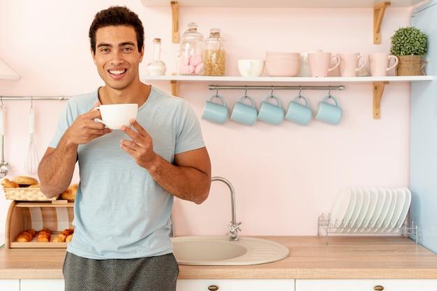 一杯のコーヒーでミディアムショットスマイリー男 無料写真