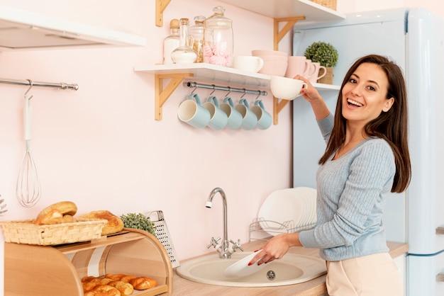 お皿を洗うミディアムショットスマイリー女性 無料写真