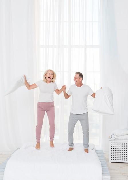ベッドでジャンプフルショットカップル 無料写真