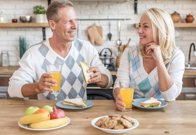 朝食を持つキッチンでミディアムショットスマイリーカップル 無料写真