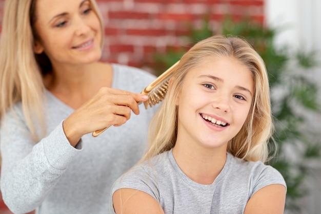 金髪の母親の娘の髪をとかす 無料写真