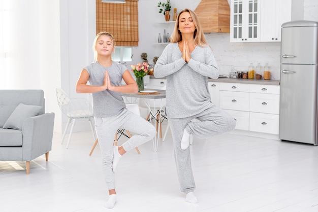 Мать и дочь делают упражнения йоги Бесплатные Фотографии