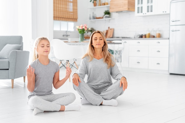 Мать и дочь медитируют в помещении Бесплатные Фотографии