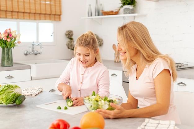 母と娘一緒に野菜を切る 無料写真