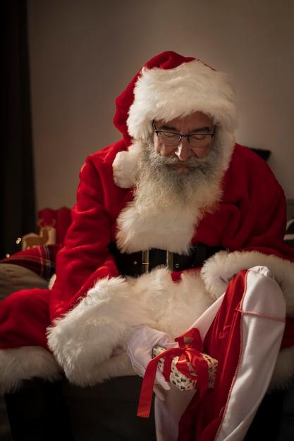 サンタクロースがプレゼントの袋を準備 無料写真