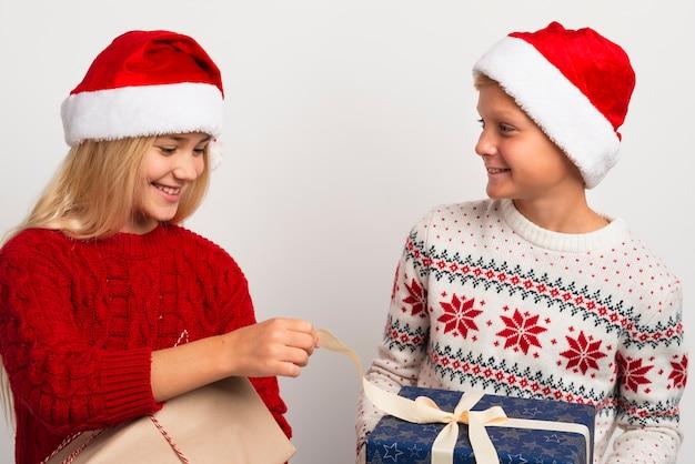 クリスマスプレゼントと友達はミディアムショット 無料写真
