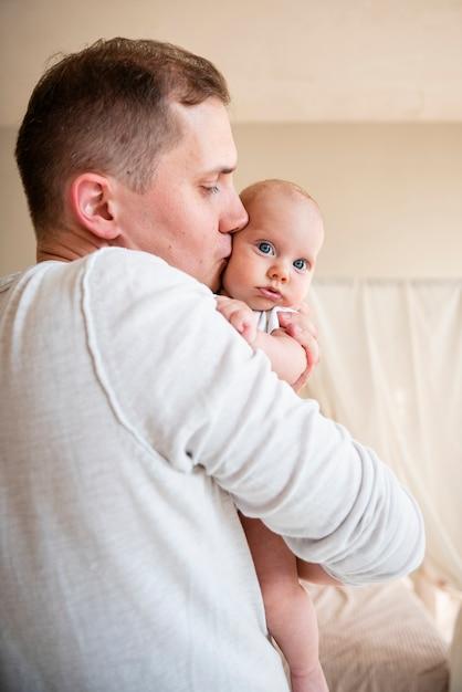 父キス新生児の側面図 無料写真