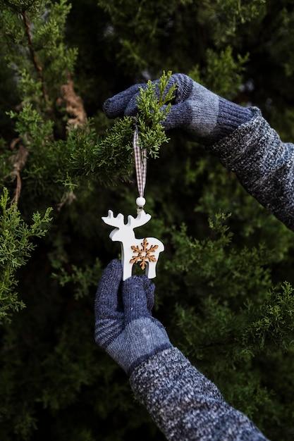 飾りでクリスマスツリーを飾る手袋でクローズアップ人 無料写真