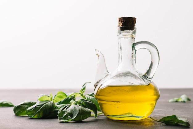 Бутылка оливкового масла, отражающая свет со шпинатом вокруг Бесплатные Фотографии