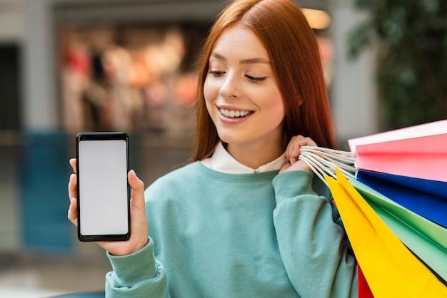 Рыжая женщина держит телефон макет Бесплатные Фотографии