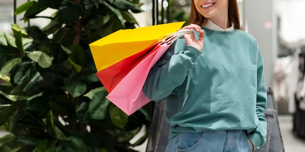 Улыбающиеся женщина, держащая бумажные пакеты Бесплатные Фотографии