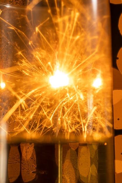 Крупным планом фейерверк отражение на бокал с шампанским Бесплатные Фотографии